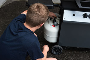 Checking propane tank under grill